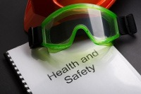 Image of a Health and Safety Courses document, a pair of goggles and a hard hat just seen in the backfround.