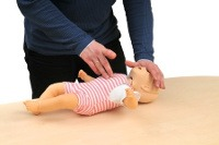 Paediatric Emergency First aid instructor sjowing CPD using a baby dummy