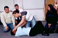image of students watching a tutor dealing with a prctice casualty at a first aid annual refresher course