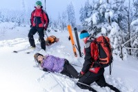 Activity First Aid team help injured woman skier lying in snow