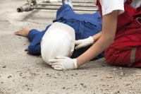 emergency first aid at work - image of a man lying on the ground being treated