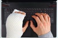 first aid in the workplace - image of someone using a computer with a bandaged hand