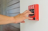 fire safety image of hand of man is pulling fire alarm
