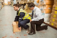 image of a worker in a warehouse lifting a box from the floor being instructed as to the correct way to lift an object as part of a manual handling course
