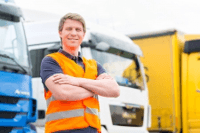 Proud lorry driver in front of lorrys having passed his CPC first aid course