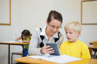 Image of a teacher and child with calculator working out the cost of an AED package